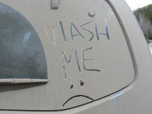 Wash Me written in dirt on car